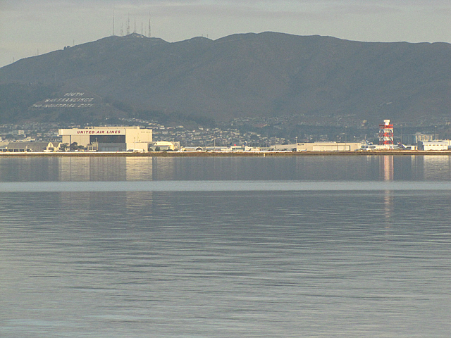 "San Bruno Mountain and the airport. The writing on the side of the mountain says ""South San Francisco Industrial City"". It not part of San Francisco, but a city in its own right."